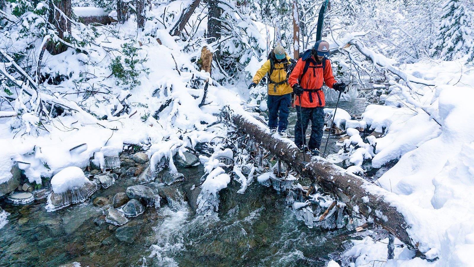 two men walking across snowy log